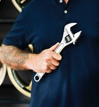 person holding silver crescent wrench behind vehicle wheels